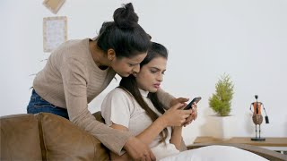 Indian girls gossiping at home while checking out something interesting in the phone