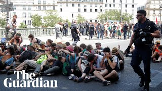 Police use pepper spray on seated climate protesters in Paris
