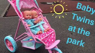Little girl takes her baby doll twins to the park in a pink Cupcake pram