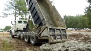 Dump trucks dumping mud