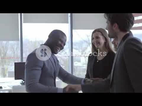 Friendly worker welcoming a colleague with a handshake and hug  Employee coming to meet funny cowork