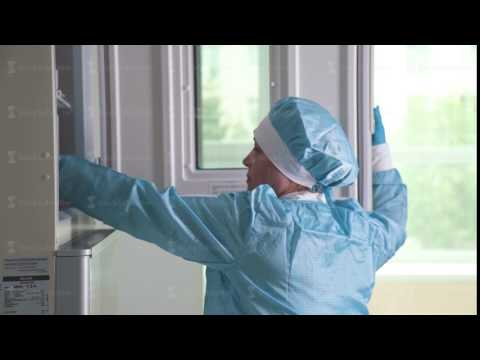 Woman lab assistant in blue sterile clothes - hat and gloves - works
