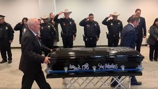 Bagpipes play and law enforcement officers salute Officer Abigail's casket following her funeral