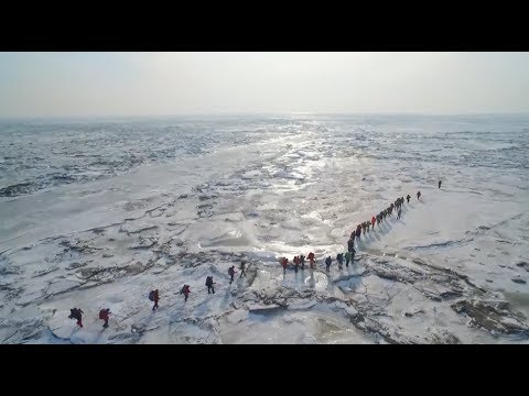 Thousands of Enthusiasts Hike on Icecap of the Frozen Sea in China
