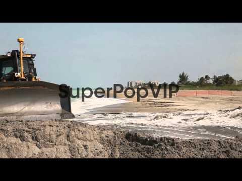 Long shot of a bulldozer pushing sand on the beach. A bul...