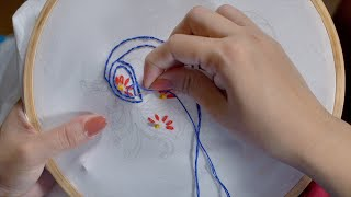 Slow motion shot of women / female / girl is embroidering stem stitch on a white fabric