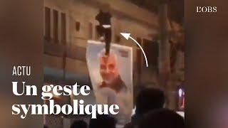 En Iran, un manifestant détache un portrait de Qassem Soleimani