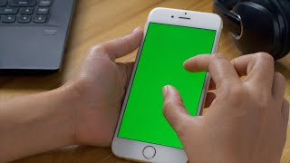 A female scrolling and clicking a smartphone with the green screen