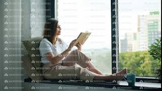 Beautiful girl reading book turning pages sitting on window-sill at home