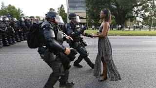 Download See Powerful Image of Woman Wearing Dress While Facing Police During Protest Mp3 and Videos