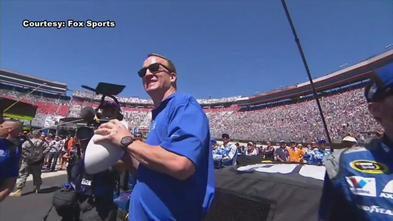 Peyton Manning is driving the Daytona pace car while Aaron Rodgers does his best to hide