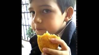 NIÑO COMIENDO EMPANADA Y HELADO AL MISMO TIEMPO