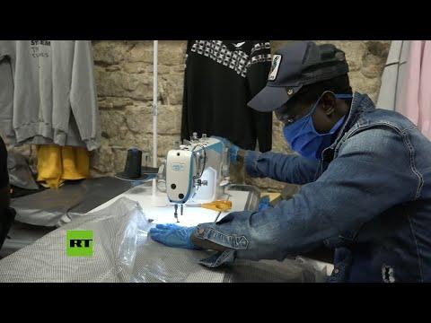 RT en Español: Manteros convierten su tienda en Barcelona en un taller de batas y mascarillas