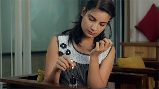 Attractive Indian girl applying black nail paint at home