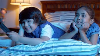 Indian siblings watching television at home during holidays - Excited and Night Time Fun. Happy Brother and Sister
