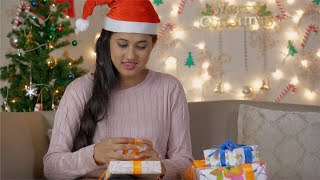 Beautiful and smiling woman wrapping / packing Christmas presents for family