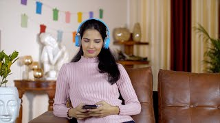 Closeup shot of an Indian girl listening to her favorite songs using her blue headphones