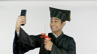 Male college grad happily taking selfies in a black robe and square academical cap