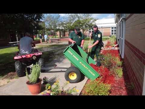 Community volunteers help cleanup the Deane Bozeman School campus after recent vandalism.