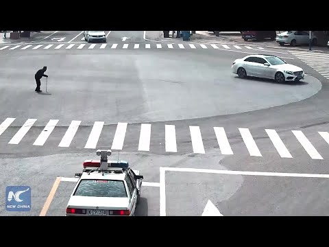 Heart-warming: Policeman carries elderly lady across street in Ma'anshan, China