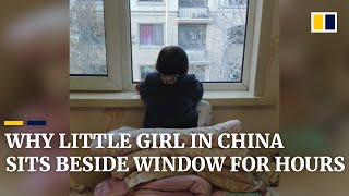 Why little girl in China sits beside window for hours