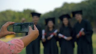 Pan shot - Woman hands clicking pictures of college pupils on graduation day