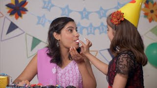 Little girl feeding birthday cake to her mother and smearing her face