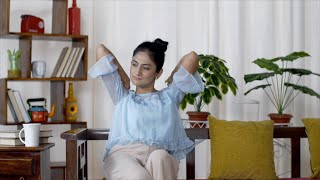 Indian teen girl stretching and relaxing her arms at home while sitting on a sofa - early morning laziness