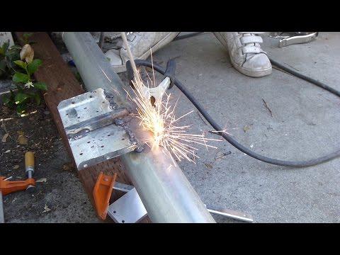 A beginner welds galvanized tubes into cantilever sliding gate frame, using BX1-200C1