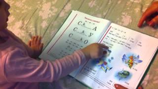 Лера читает букварь.