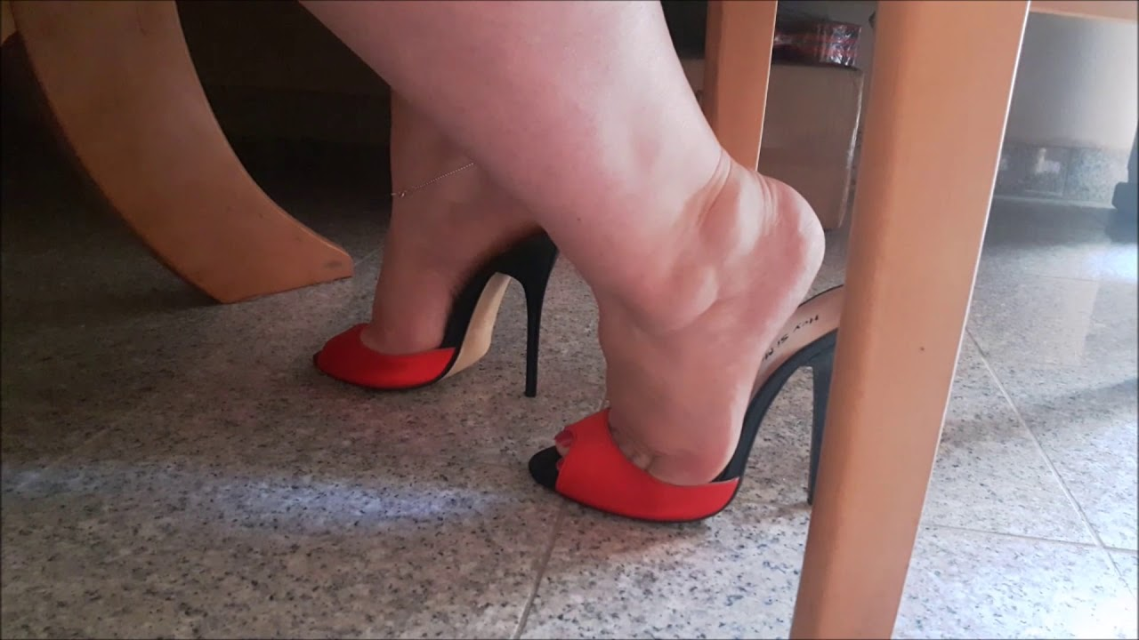 red high heel mules under table
