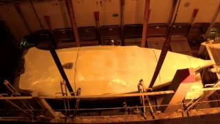 Sail boat loaded beneath deck of a container ship in transit