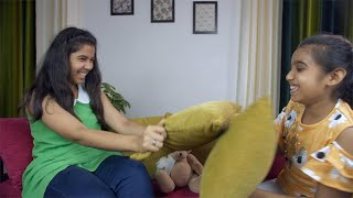 Pretty Indian girls happily fighting with cushions while sitting on a couch - cheerful siblings