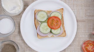 A girl under the process of making a healthy vegetable sandwich