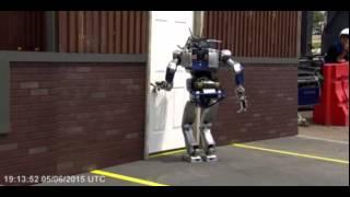 Robot tries to open door, falls down.