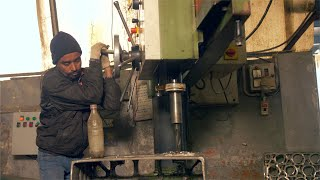An Indian laborer working on a manual drilling machine - technology concept
