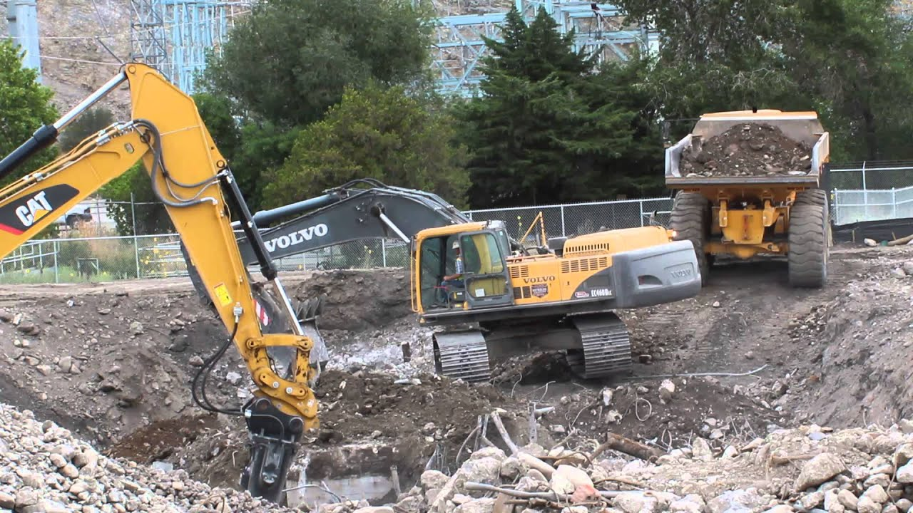 CAT Excavator using and impact hammer attachment while Volvo Ecavator loads an articualted dump ...