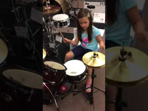 4 years old girl is drumming with muscles