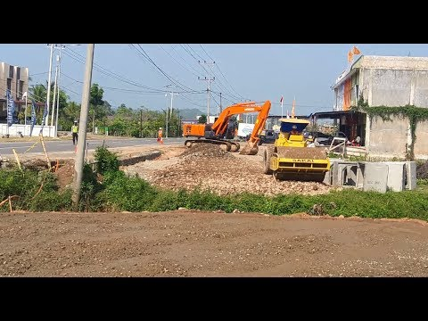 Excavator HITACHI Zaxis 200 and compactor SAKAI SV512D H work on access road in meureudu, Aceh