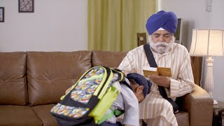 Indian grandson touching his grandfather's feet for blessings before going to the school - Old man reading Sikh Hymns or Banis from Gutka