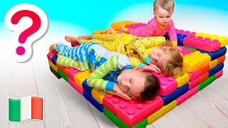 Cinque Bambini giocano con il gigantesco lettino LEGO