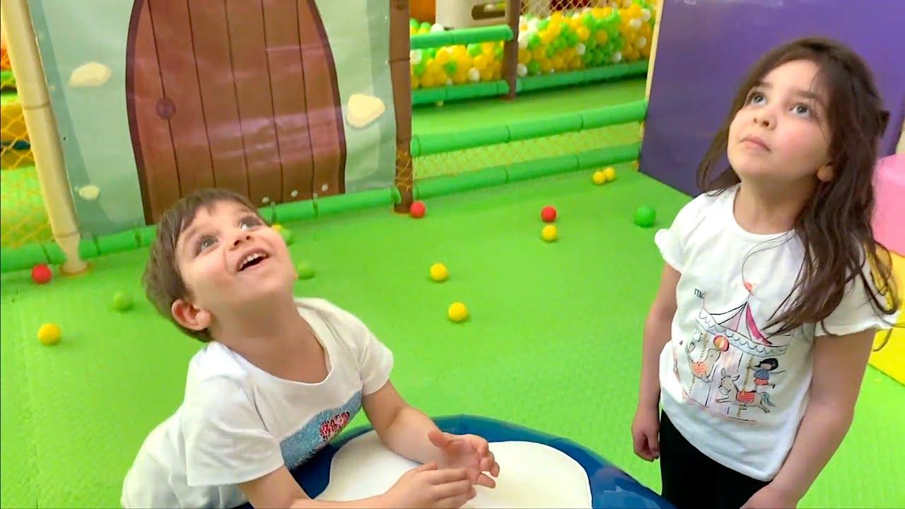 Oyun parkında top fırlatma oyunu Azra ve Selim'in oyun alanındaki renkli toplarla kapışması