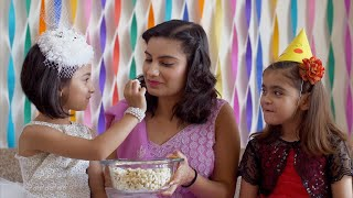 Cute little girl feeds popcorn to her beautiful mother on her birthday - Happy Indian Family