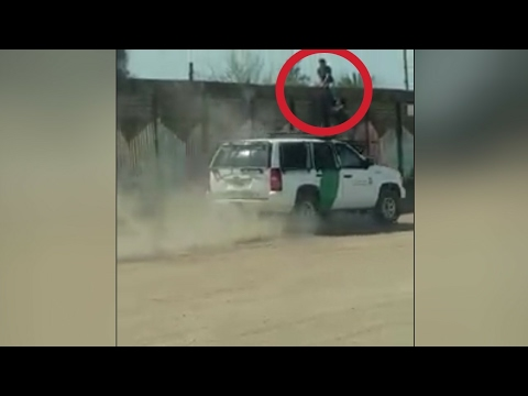 Mexican Crossing The Border Next To A Border Patrol Vehicle