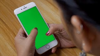 Pan shot of female scrolling her smartphone with the green screen