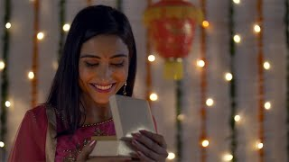 Young attractive woman in traditional wear smiling and opening a Diwali gift box