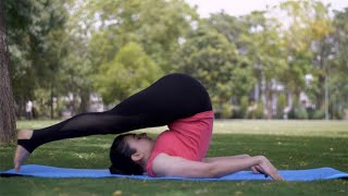Healthy beautiful lady practicing Halasana (plough pose) on a yoga mat - sportswear