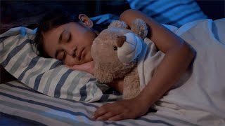 Cute little girl sleeping in her bed with her soft toy - nightlight
