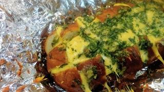 Запеченный батон с чесноком, зеленью и сыром.