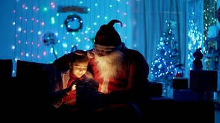 Bokeh shot of cute Indian kid opening a magical gift box with old Santa Claus - festive scene
